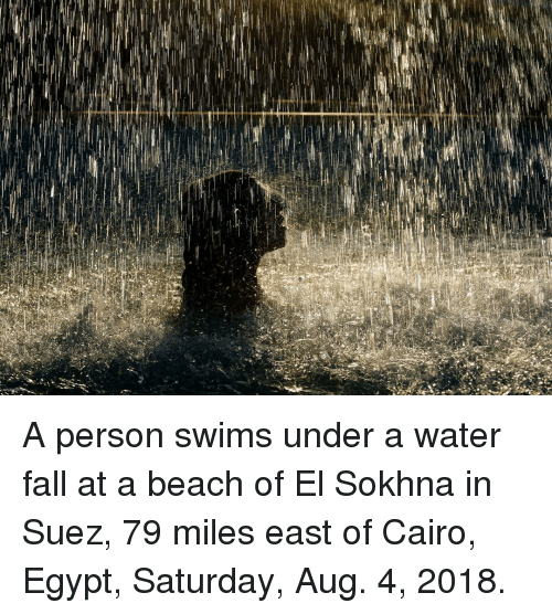 Fall, Memes, and Beach: A person swims under a water fall at a beach of El Sokhna in Suez, 79 miles east of Cairo, Egypt, Saturday, Aug. 4, 2018.