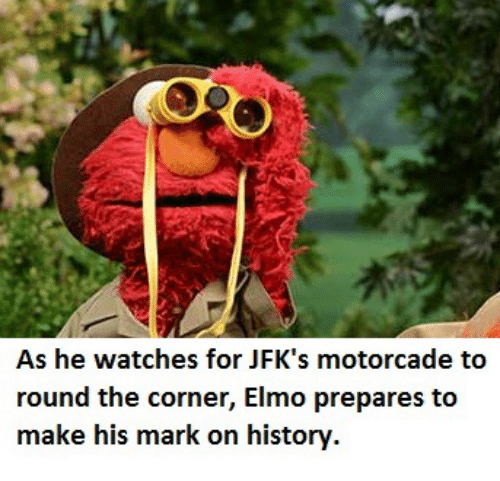 Elmo, Watches, and Make: As he watches for JFK's motorcade to  round the corner, Elmo prepares to  make his mark on historv.