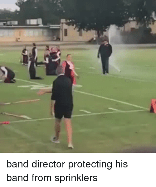sprinklers: band director protecting his band from sprinklers