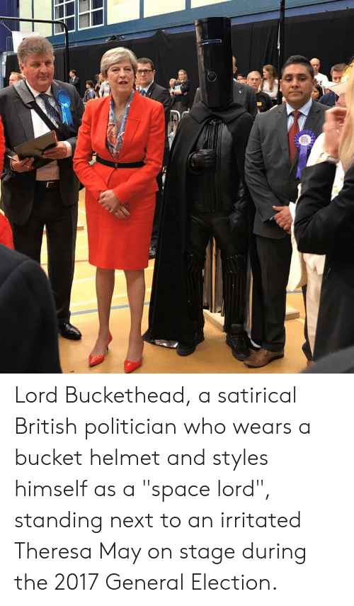 """Lord Buckethead: EE Lord Buckethead, a satirical British politician who wears a bucket helmet and styles himself as a """"space lord"""", standing next to an irritated Theresa May on stage during the 2017 General Election."""