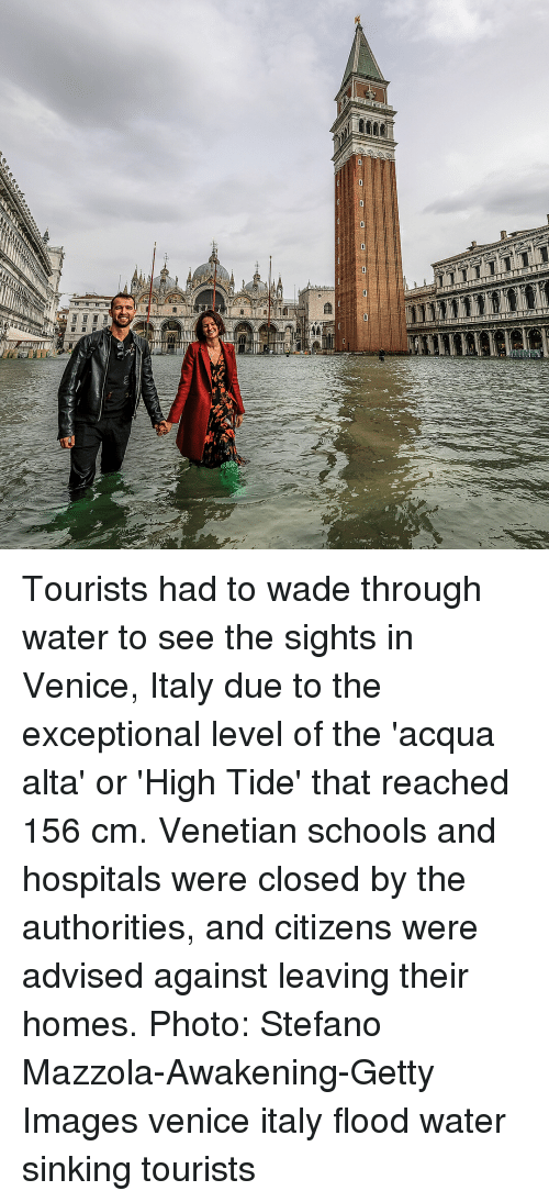 sinking: Tourists had to wade through water to see the sights in Venice, Italy due to the exceptional level of the 'acqua alta' or 'High Tide' that reached 156 cm. Venetian schools and hospitals were closed by the authorities, and citizens were advised against leaving their homes. Photo: Stefano Mazzola-Awakening-Getty Images venice italy flood water sinking tourists