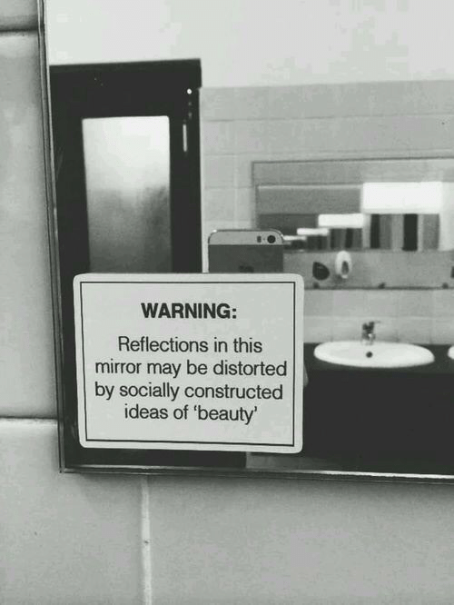 Mirror, Ideas, and May: WARNING:  Reflections in this  mirror may be distorted  by socially constructed  ideas of 'beauty'